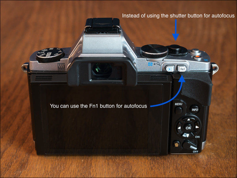 Use the Fn1 button on the Olympus OM-D E-M5 to activate autofocus.