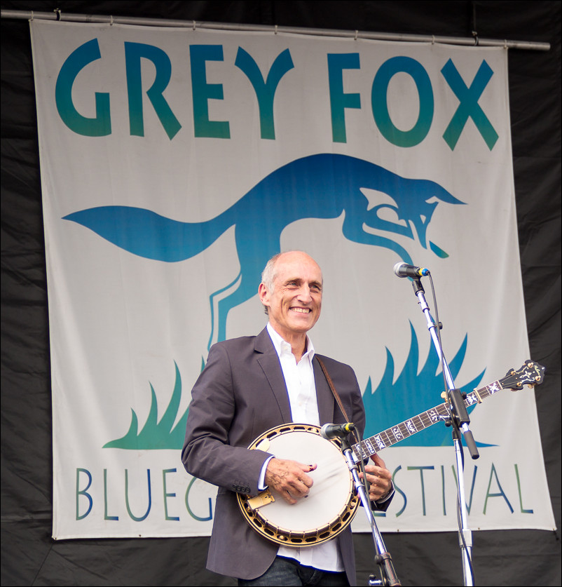 After cropping.  Isolating the banjo player with the festival sign directly behind him makes this a more powerful photo.