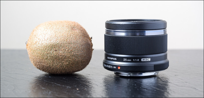 The Olympus 25mm f/1.8 is tiny, about as big as a kiwi fruit.