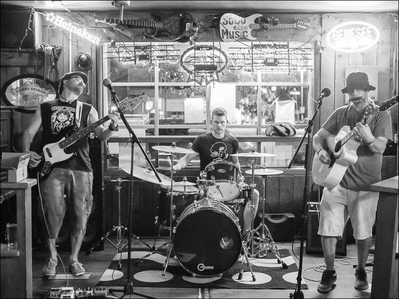 The Olympus 25mm f/1.8 is wide enough to capture the whole band in a fairly tight space.  This was shot at 1/50 sec at ISO 3200.